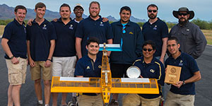 Georgia Tech Design Competition team with their model and third place plaque at the 2015 AIAA Design Build Fly competition, in Tuscon, AZ.