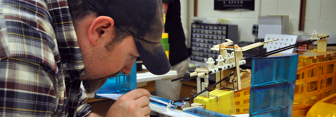 Aerospace engineering student putting final touches on a model aircraft that will be entered into a design competition