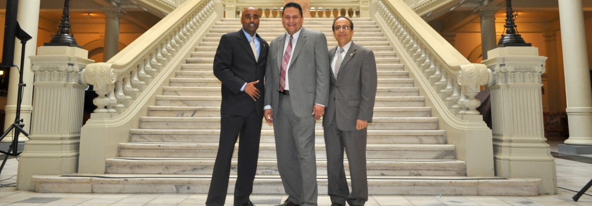 Dr. Ruffin,    , and        standing in front of a grand marble staircase at      .