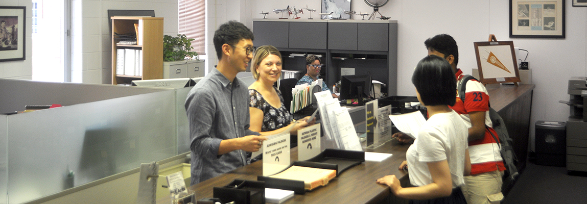 2 students receiving helpful forms from 2 AE Academic Office staff members