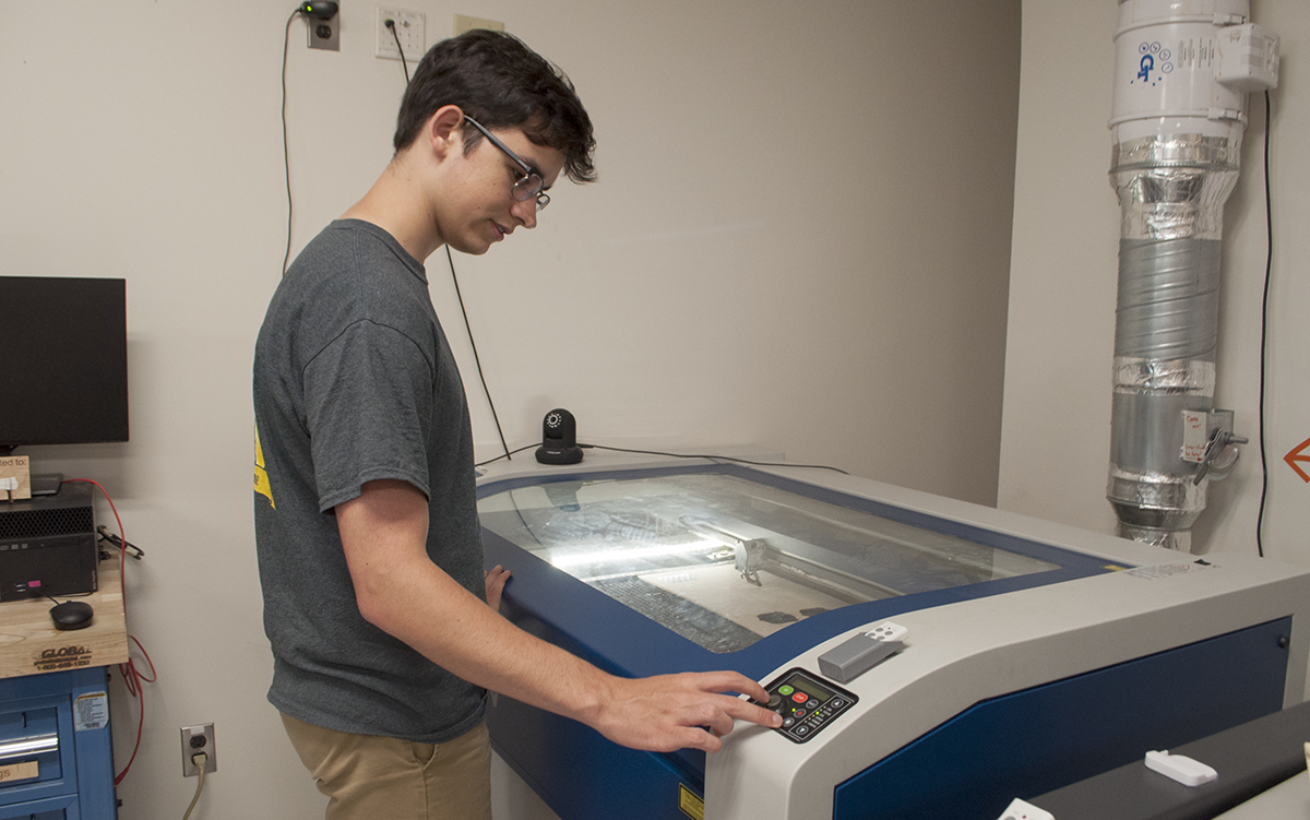 Aero Maker Space Mentor, Alex Bustos working with the laser cutter